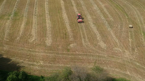 Agriculture tractor rolling dry hay bales on meadow, aerial view Live Action