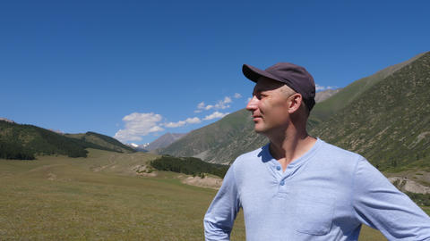 Adult man enjoying mountain view and breathing fresh air in valley Live Action