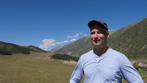 Portrait adult man standing on mountain landscape and enjoying fresh air Live Action