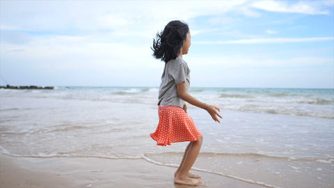 Asian little girl playing on the beach with nature sea wave coast for summer vacation concept Footage