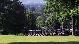 Golf carts lined up on a golf course. Establishing shot at a golf range in the Footage