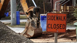 Sidewalk closed sign at a construction sight with a crane digging dirt in the Footage