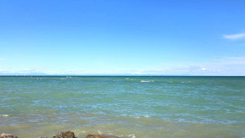 View to sea line at sunny day: wave splash near stone shore Footage