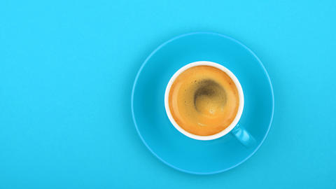 Full white cup of espresso coffee on blue GIF