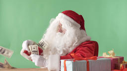 Satisfied Santa Claus throwing bills out of a bundle money on table, money Footage