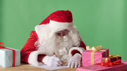Funny Santa Claus writes a letter, looks at the camera and waves his hand Footage