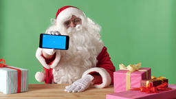 Smiling Santa Claus showing smartphone in camera, gifts on the table, chromakey Footage