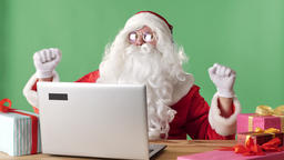 Smiling Santa Claus sits behind a laptop listening to music on headphones and Footage