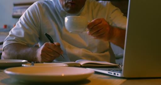Chef writing on diary while having coffee 4k Footage