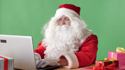 Serious Santa claus sitting working on laptop, prints, office worker, green Footage