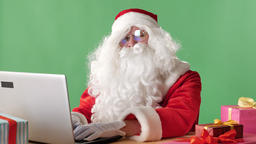 Serious Santa Claus sitting working on laptop, typing, Looking at camera and Footage