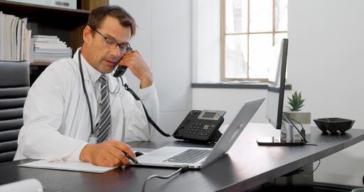 Physician talking on landline at desk 4k Live Action