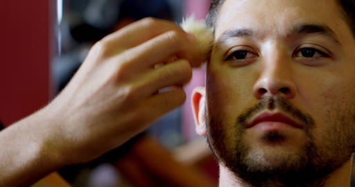 Barber cleaning hair from customer face after trimming hair 4k Footage