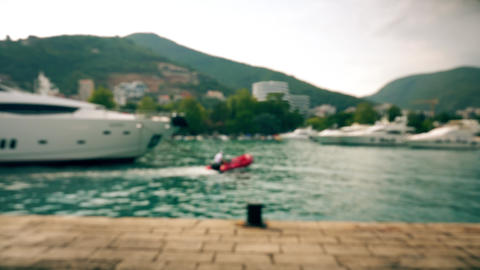 Defocused moored luxury motor yachts and red motor boat at marina Live Action