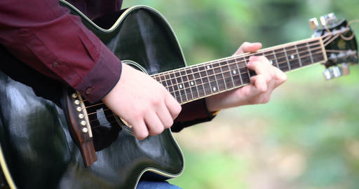 Young man playing acoustic guitar artist musician outdoors GIF
