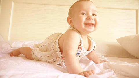 Funny baby learning to crawl in bed Footage