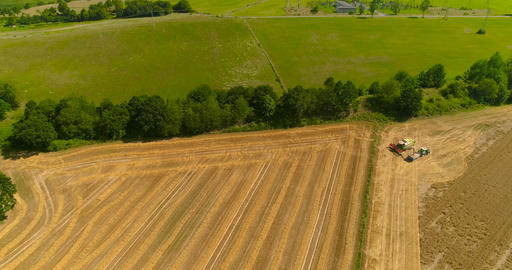 Combine harvester and tractor working in agricultural field Footage