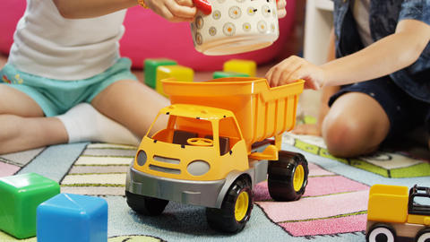kids play with yellow tipper truck and toy pan in children room Archivo