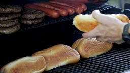 Hamburgers, hotdogs and buns on a barbeque grill. Gourmet fast food cuisine at a Footage