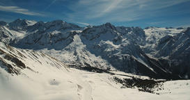 Jagged Snow Covered Mountains and Bright Sunshine Footage