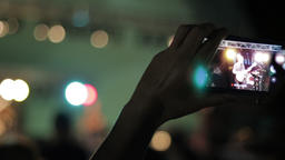 Viewing A Concert Through A Phone Screen. Recording a live music show with a Footage