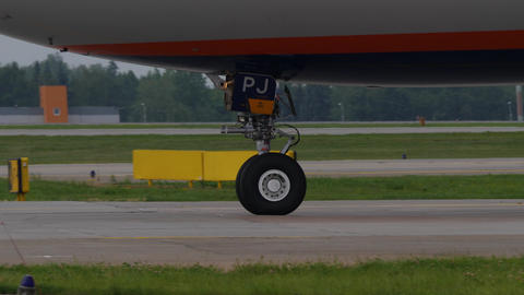 Landing gear of taxiing aircraft. Fore wheel and part of fuselage of an airplane Footage