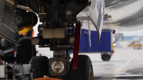 Undercarriage of parked airplane with red warning Remove before flying ribbon GIF