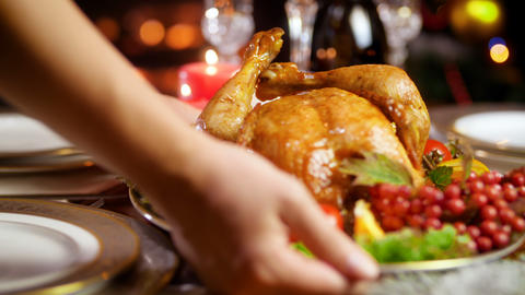 Closeup 4k footage of young woman putting dish with baked chicken on dinner Footage