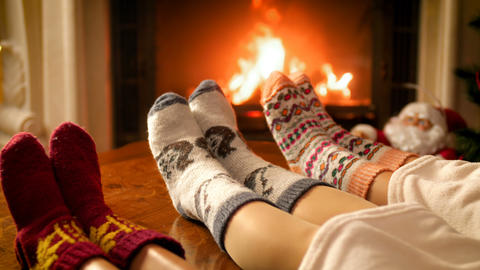 Closeup 4k footage of family feet lying on sofa under blanket warming at burning Live Action