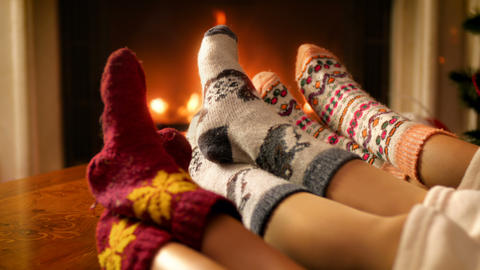 Closeup 4k video of parents with child wearing woolen knitted socks relaxing by Footage
