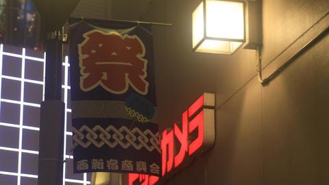Flag and neon board including Japanese chracter at Shinjuku low angle ビデオ