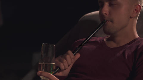 Handsome guy holding a glass of champagne and smoking a hookah Footage