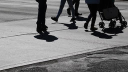 Close up of peoples legs walking across the street. People in silhouette Footage