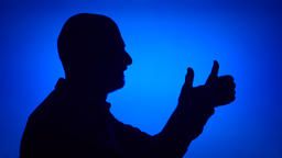 Silhouette of senior man make thumb up on blue background. Male's face in Footage