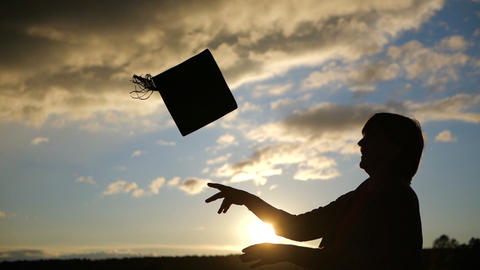 Woman celebrate finish of her education. She throw her hat in slow motion Footage