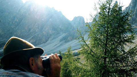 elderly man looks through the binoculars towards the mountains Archivo