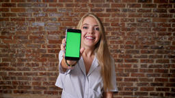 Young caucasian blonde using a smartphone showing a smartphone screen, green Footage