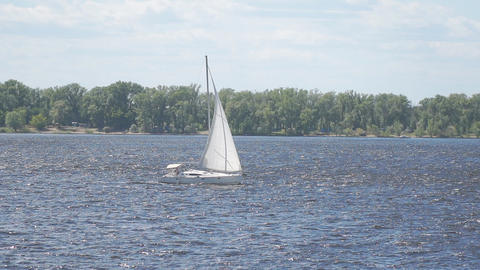 A white sailboat sails along the river in the background of a forest on the Live Action