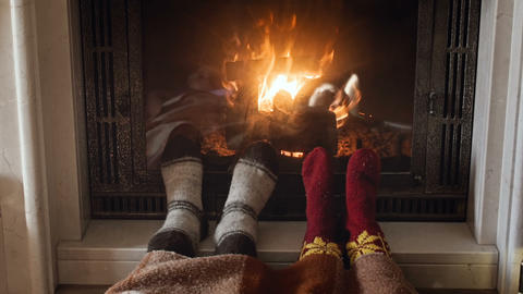 4k footage of two people warming their feet in woolen knitted socks at burning Footage