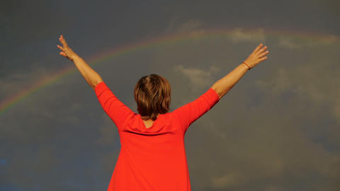 Back shot of woman that rise her hands into the sky during rainbow weather GIF