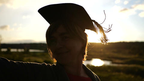 Silhouette of middle aged woman that standing at sunset in student hat Footage