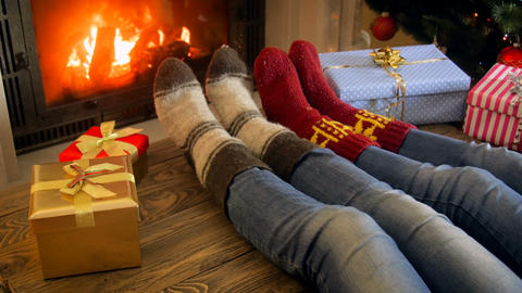 Closeup 4k footage of family wearing woolen socks relaxing by the fireplace on Footage