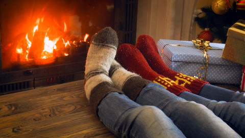 4k video of family in knitted woolen socks resting next to Christmas tree at Footage