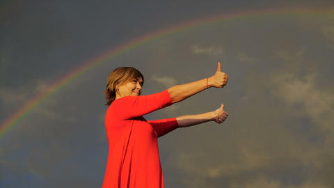 Middle aged woman show thumbs and smile during rainbow Footage