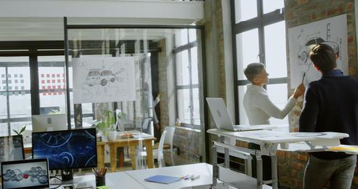 Car designers discussing over car sketch design 4k Live Action