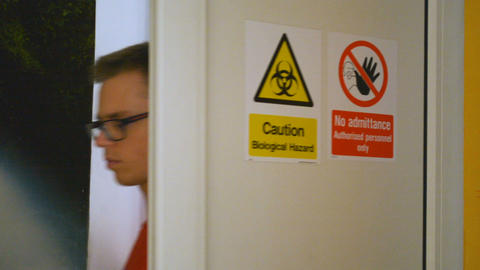 Caution Biological Hazard and No Admittance warning danger signs on the door Footage