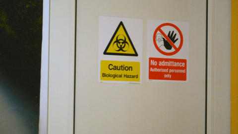 Scientist enters and leaves bio laboratory, warning sign Biological hazard on Footage
