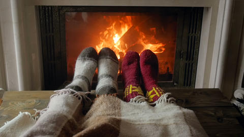Slow motion video of roamntic couple lying under blanket and warming feet by Live Action