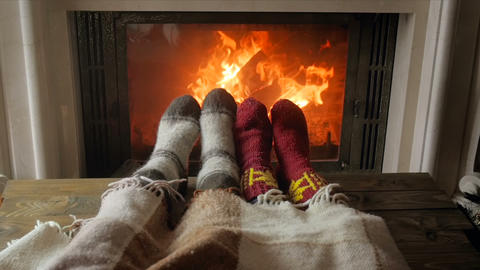 Closeup slow motion video of couple in love in warm socks lying under blanket at Live Action