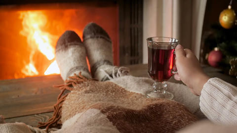 Closeup slow motion video of woman warming feet at fireplace and drinking hot Footage